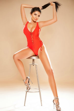 Jojo posing in a red body outfit for Movida Escorts.