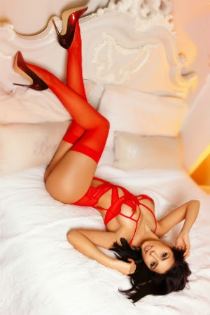 Fatima on her bed in red lingerie