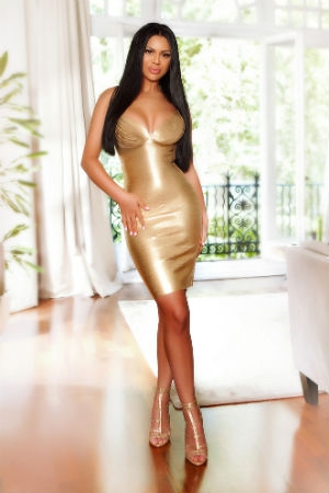 Sensual babe from Movida Escorts in a gold dress.
