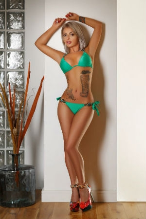Tattooed escort Benita in a green bikini