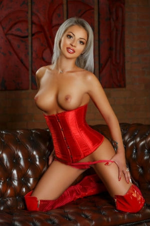 Benita topless with a red corset on