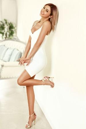 A stunning blonde wearing a white dress.