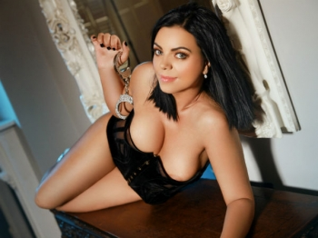 Slava is posing for Movida Escorts wearing a corset.