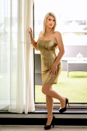 Mirage wearing a golden dress.