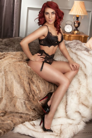 Lady with red hair posing for Movida Escorts