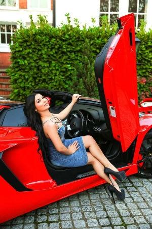 Deima posing in a red car