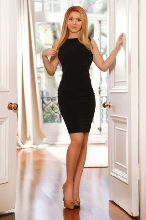 Petite blonde dressed in a black dress