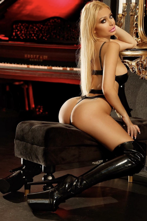 Marlene wearing a black outfit and very sexy high boots