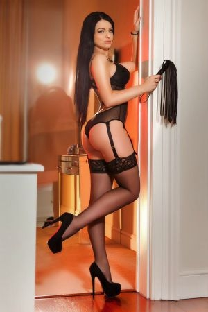 Justina dressed in a black body outfit and stockings
