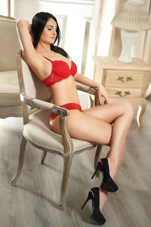 Marina sat in a chair with red lingerie on