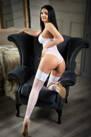 Marina in a white bra and thong as she kneels on a chair