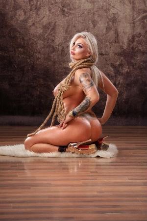 Tattooed blonde posing naked