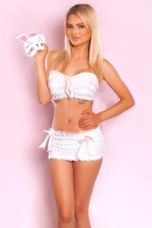 Belinda wearing a white skirt and crop top
