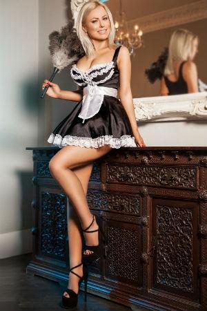A sexy maid leans against a closet