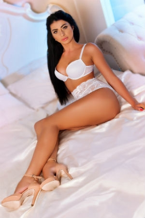 Taisa lies on the bed wearing white lingerie