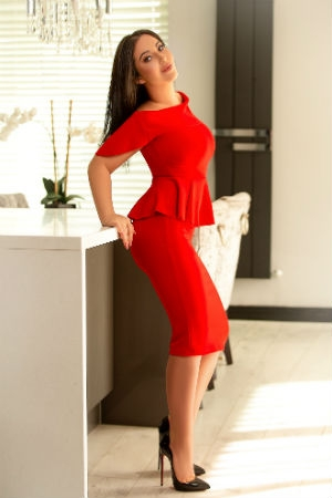 Alina leaning on kitchen counter-top in red dress