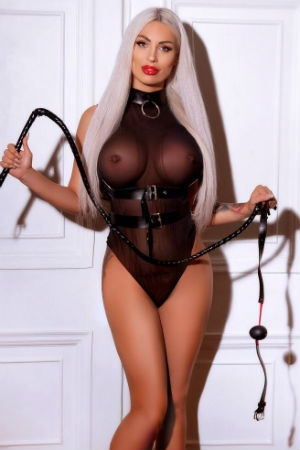 Aylin in latex top holding whip