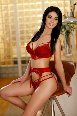 Glory reclines on a bar stool wearing red lingerie