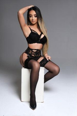 Alegra sitting on white box wearing black underwear