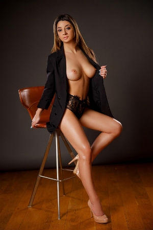 A tall young escort poses in a black jacket