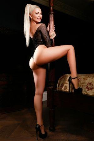 Angelina posing against bed post in black bodysuit