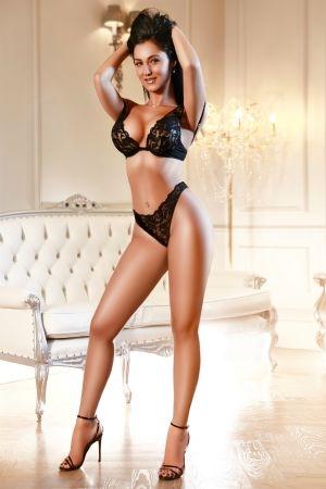 Amelinda posing in black lingerie in front of white sofa