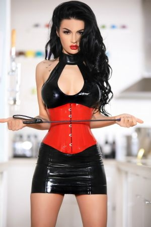 Escort Darcie wearing dom outfit with whip for escorting encounters
