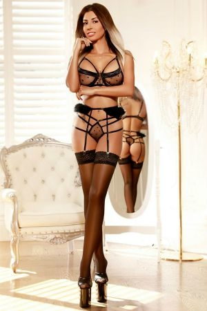 Slim escort dressed in a black set of lingerie