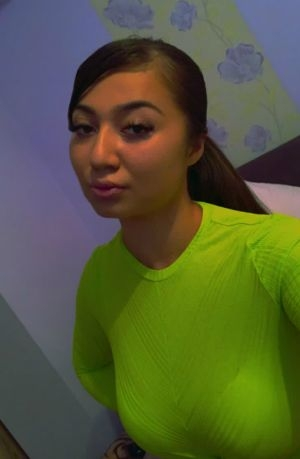 Young escort takes a selfie in her green t-shirt