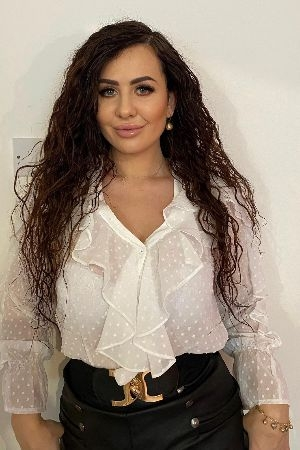 Amira wearing a spotted white blouse