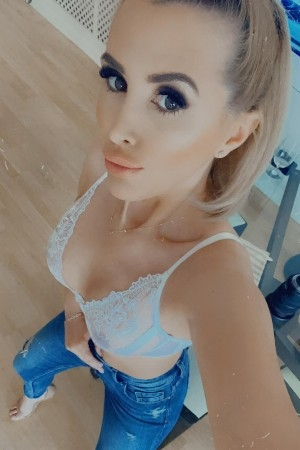Alina taking a selfie wearing white bra and denim jeans