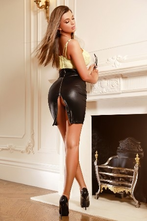 Blaise wearing a black latex skirt and yellow top
